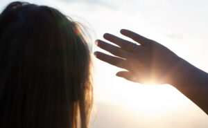 Back close-up shot of a woman looking in the distance hiding from the sun with a hand